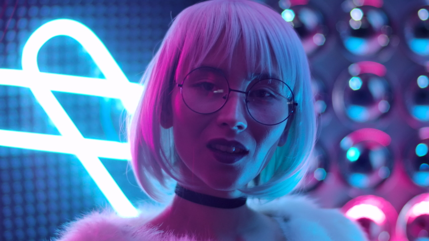 Portrait Beautiful Trendy Girl In Glasses Looking At Camera and Smile. Confident and Attractive Woman with Open Eyes in Purple Blue Light Posing at Party. Cute 20s Female Closeup in Colourful Pink 4K | Shutterstock HD Video #1039079750