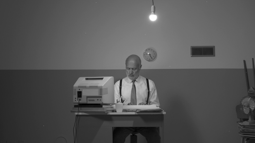 Sad senior businessman working with an outdated computer on a small desk, he is sad and disappointed | Shutterstock HD Video #1039160570