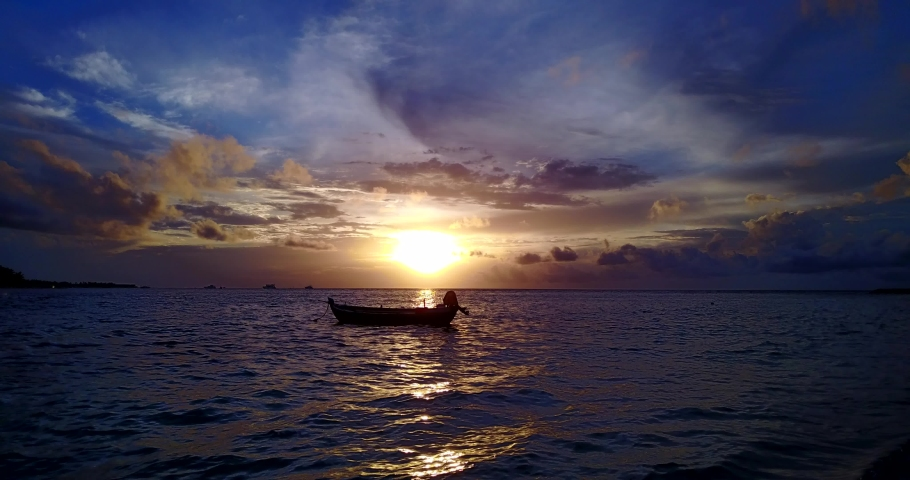 Lonely boat in the sea at bright yellow orange sunset | Shutterstock HD Video #1039337750