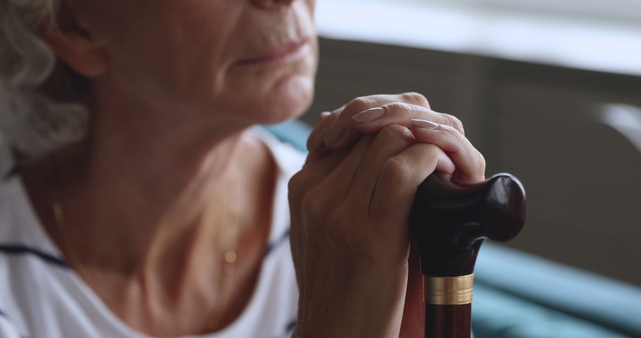 Disabled old senior grandmother holding walking cane stick in hands, sad elderly woman hopeless depressed about health problem injury worried of disease concept alone at home hospital, close up view | Shutterstock HD Video #1039337870