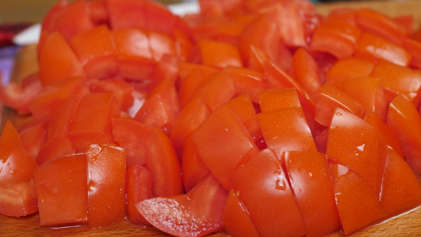 Sliced red tomato on chopping board. Preparing fresh ripe salad or cooking slicing vegetables #1039704020