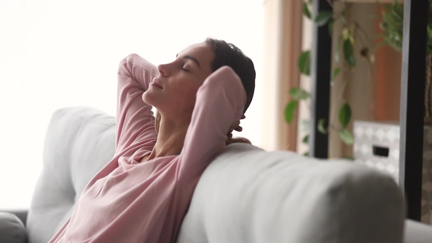 Moving camera slider showing side view relaxed millennial woman falling asleep closed eyes putting hands behind head leaned on couch enjoy day nap in living room, resting at home renew energy concept | Shutterstock HD Video #1039785860