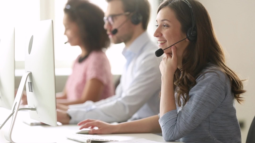 Service phone operators sit at shared desk focus on sales agent woman in headset use pc answers incoming calls talk with client provide professional support to customers sell company product concept | Shutterstock HD Video #1039793780
