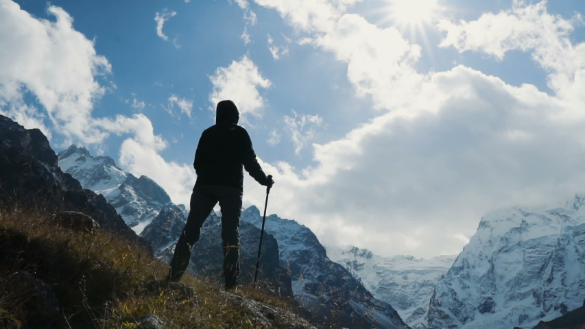 Hiker woman walking the edge of the canyon raising hands up at sunset. Enjoying nature vacation travel adventure at Caucasus mountains. Slow motion. #1039887350
