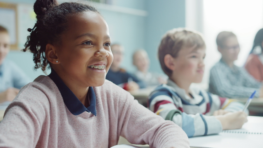 In Elementary School Class: Portrait of a Brilliant Black Girl with Braces Writes in Exercise Notebook, Smiles. Junior Classroom with Diverse Group of Bright Children Working Diligently and Learning