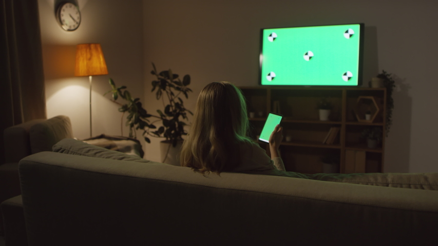 Rear view shot of unrecognizable woman sitting on couch in dark living room and using mobile phone with chromakey while watching TV | Shutterstock HD Video #1040076860