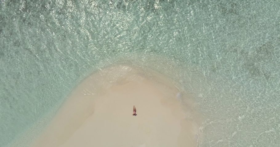 Aerial view of a sandbank in the Maldives sea - A young woman is lying on the white sand while looking at the sea | Shutterstock HD Video #1040115050