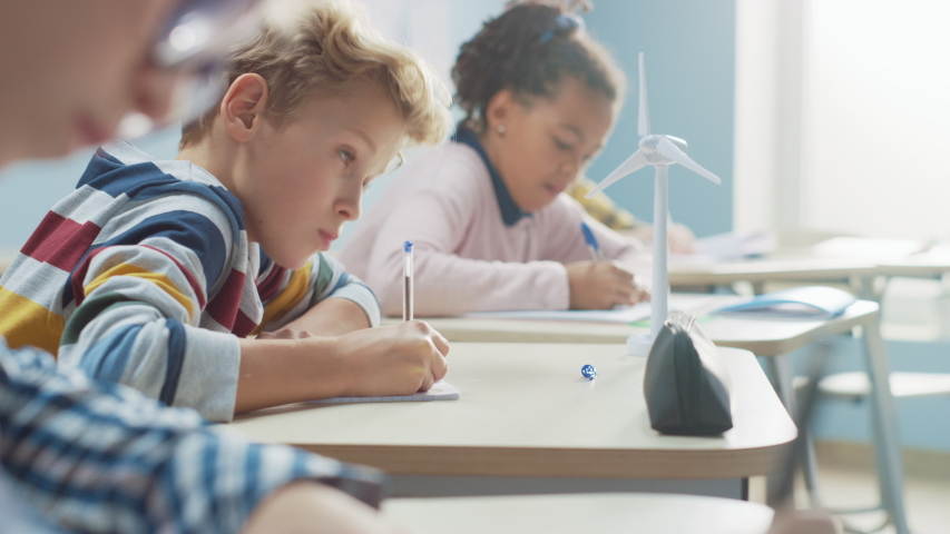 In Elementary School Classroom Brilliant Caucasian Boy Writes in Exercise Notebook, Taking Test and Writing Exam. Junior Classroom with Diverse Group of Bright Children Working Diligently and Learning