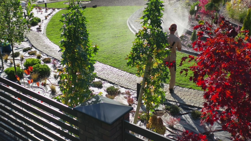 Caucasian Professional Gardener Watering Newly Developed Residential Garden Using a Hose. Sunny Fall Day. | Shutterstock HD Video #1040289470