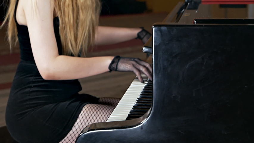 A girl in a black dress and with a mask on her face plays the piano. Unusual musical performance | Shutterstock HD Video #1040290400