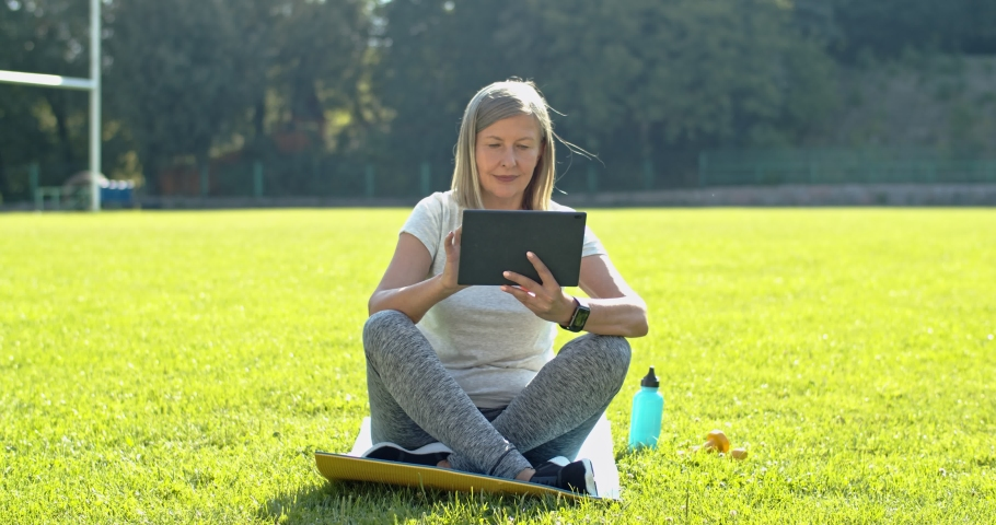 Caucasian senior woman sitting on the mat on the freen grass of the stadium and using tablet device, tapping, scrolling and watching something on the screen about sport in the morning. | Shutterstock HD Video #1040336090
