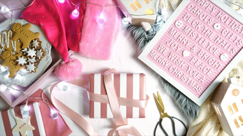 On-trend stylish Christmas flat lay, cozy in bed or indoors wrapping gifts with warm sweater, gifts and letter board. Stop motion animation. Wrapping gift. | Shutterstock HD Video #1040368520