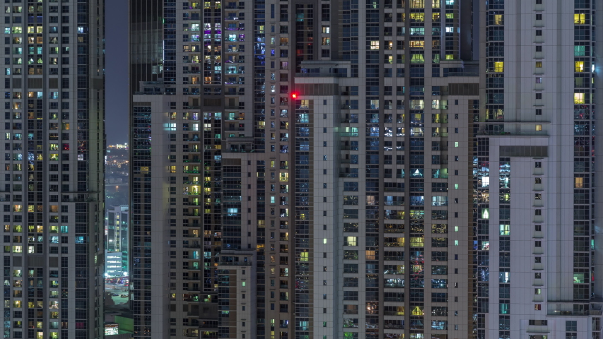 Lights from windows of offices and apartments aerial timelapse. Skyscrapers with working people in the evening in Business Bay, Dubai, United Arab Emirates. Complex of towers at night | Shutterstock HD Video #1040416880