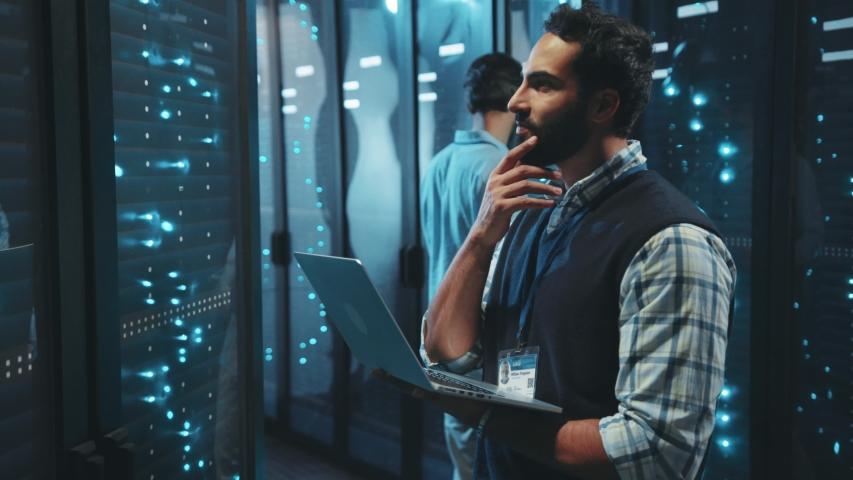 Bearded server specialist using computer laptop running diagnostics on server rack cabinets inspecting digital room of data center. | Shutterstock HD Video #1040450090