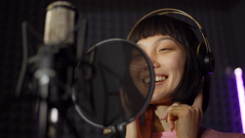 Closeup from below shot of young female Asian pop artist in earphones smiling while performing joyful song in microphone standing in booth in music recording studio #1040533670