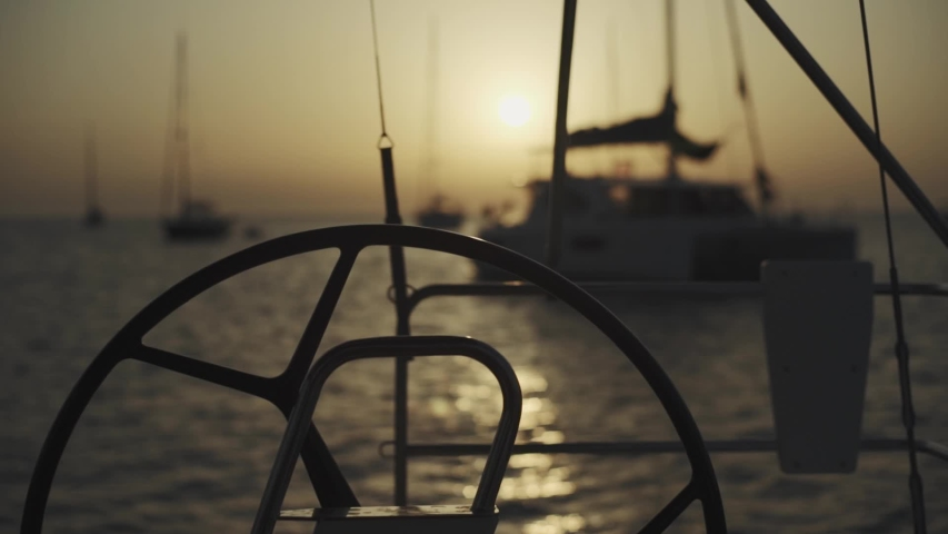 Many yachts in a bay on Formentera island. Incredible sunset in Cala Saona bay. Silhouettes of unrecognizable people on yachts | Shutterstock HD Video #1040589230
