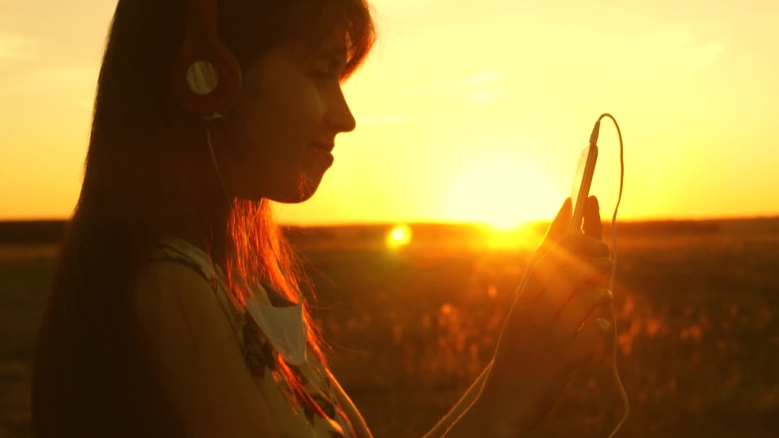 beautiful woman travels listening to music and dancing in rays of beautiful sunset. young girl in headphones and with a smartphone touches finger to sensor of tablet selects songs online. Slow motion #1040734790