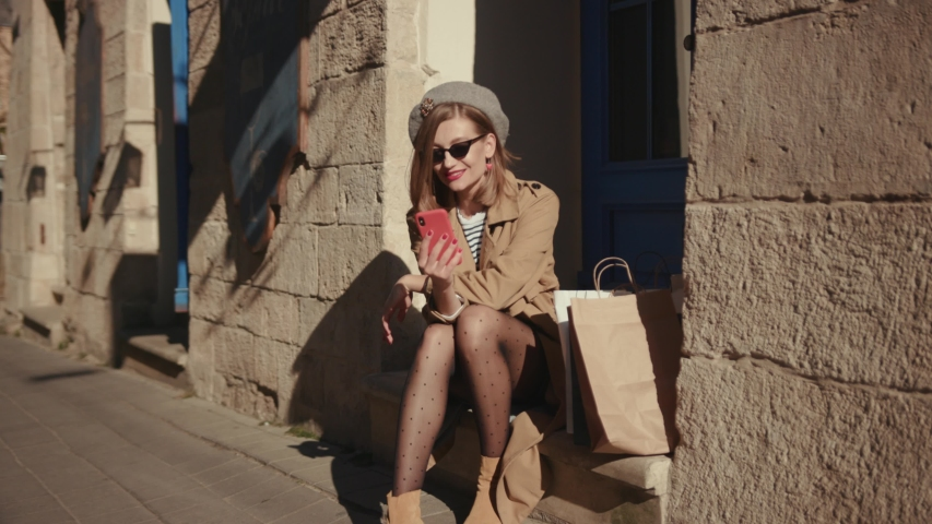 Beautiful young woman wearing stylish coat in a bright sunlight uses phone sitting in the city center looks around smile happy summer internet business outside technology mobile slow motion #1040737910