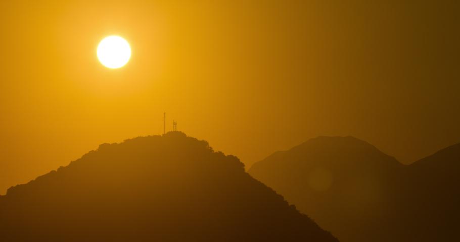 Timelapse of sun setting behind a hill, taken in Hong Kong   Shutterstock HD Video #1040820530