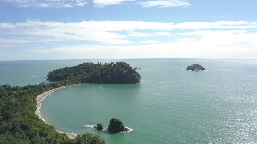 Aerial view of Manuel Antonio National Park in Costa Rica. Drone flies over the tropical sand beach, Cathedral Point, Playa Biesanz. | Shutterstock HD Video #1040821580