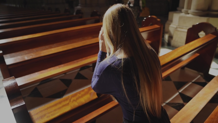 This video shows a young caucasian woman kneeling and praying at beautiful catholic church pew, rear view with sun beaming down.