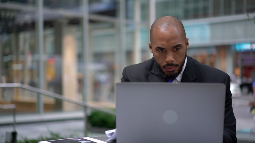 African American man intelligent managing director keyboarding on laptop computer while sitting in cafe terrace, male economist analyzing activities of company via netbook and financial reports | Shutterstock HD Video #1040953850