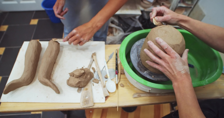 Top closeup view of female hands modeling and creating ceramic vase flowerpot on professional pottery table in modern private art school studio. Hobby arts education. Creative process.   Shutterstock HD Video #1041084520