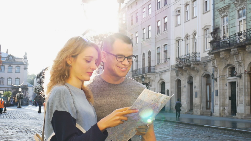 Young couple watching the city map and searching for direction early in the morning on empty ancient square somewhere in Europe, travelling concept | Shutterstock HD Video #1041090190