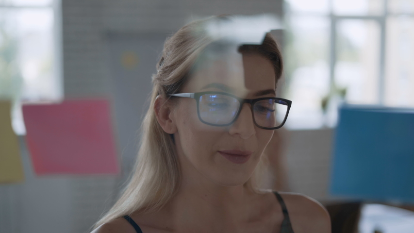 Modern successful blond woman working in an office on a project. woman stands in front of a transparent board with notes 4K | Shutterstock HD Video #1041441370