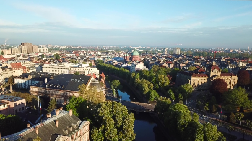 Aerial panoramic view of the cityscape. Beautiful old houses, surrounded by green trees , river and bridge. Taken by drone at early morning. Strasbourg, France.   | Shutterstock HD Video #1041468100
