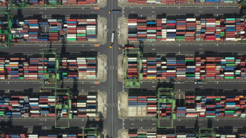 Stunning aerial view of the port of Singapore with trucks and thousands of colored containers ready to be loading on the cargo ships. The Port of Singapore is the second biggest port in the world.   Shutterstock HD Video #1041547840