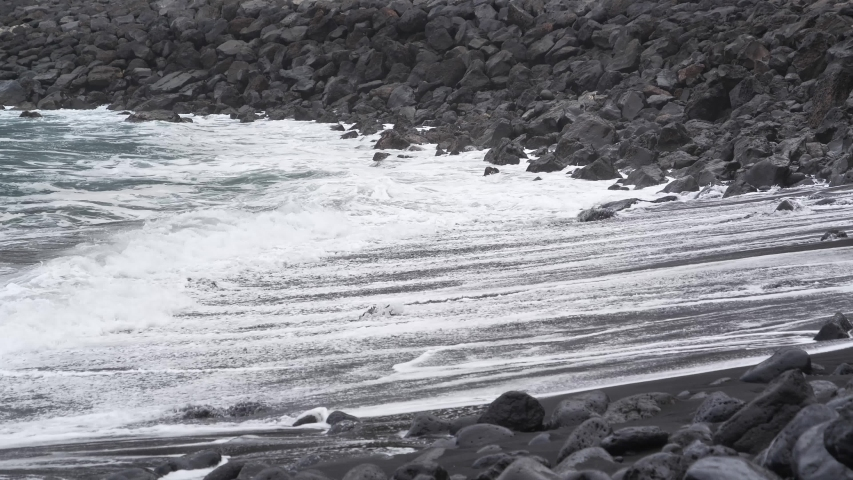 White foamy breaking waves on the beach with black volcanic sand on Tenerife, Canary islands, Atlantic ocean, Spain