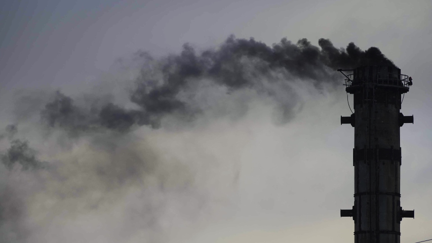 Black smoking pipes, air pollution concept. Industrial factory pollution, global warming. Industrial zone with big pipe smoking, black smoke. Environmental problems.