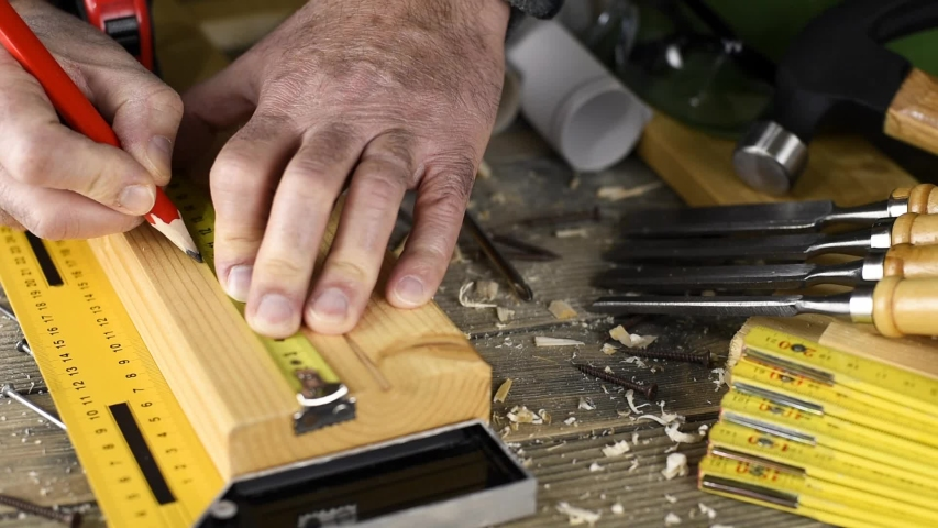 Top view. Carpenter measures a wooden board and with the pencil and the carpenter's square drawing the cutting line. Construction industry, do it yourself. Wooden work table. | Shutterstock HD Video #1041786640