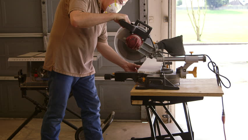 A tradesman or handyman homeowner type using a power miter saw to cut a board for a home improvement project.