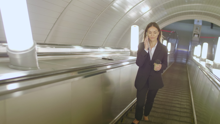 Young female clerk going up on escalator in subway and talking on smartphone with her business partner | Shutterstock HD Video #1042093720
