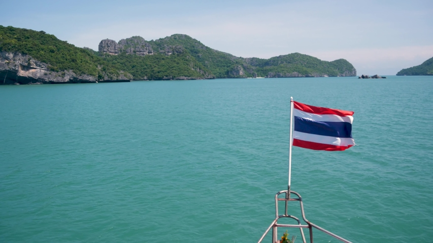 Group of Islands in ocean at Ang Thong National Marine Park. Archipelago in the Gulf of Thailand. Idyllic turquoise sea natural background with copy space. Waving flag as national symbol on the boat | Shutterstock HD Video #1042108030