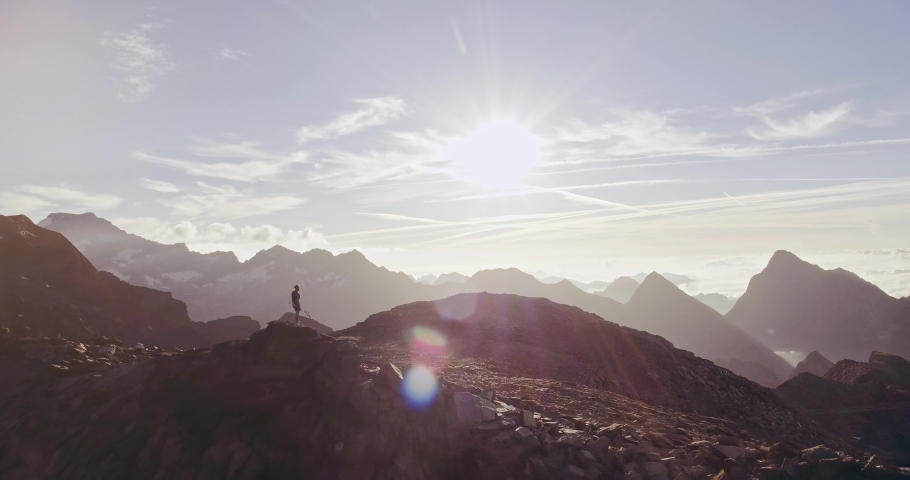 Aerial trail runner man standing on mountain top peak goal looking horizon view.drone shot.Wild nature outdoors at sunrise or sunset backlit.Training activity,sport,effort,challenge,willpower concepts | Shutterstock HD Video #1042156840