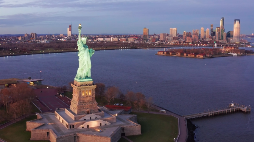 Slow drone panning along The Statue of Liberty, Jersey City and New York City skylines. The Statue of Liberty is a colossal neoclassical sculpture on Liberty Island in New York Harbor. | Shutterstock HD Video #1042235110