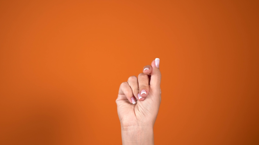 Closeup view of female hand with beautiful natural french design pink and white manicured nails isolated on orange background. Happy woman snapping her fingers cheerfully. Real time 4k video footage. | Shutterstock HD Video #1042251490