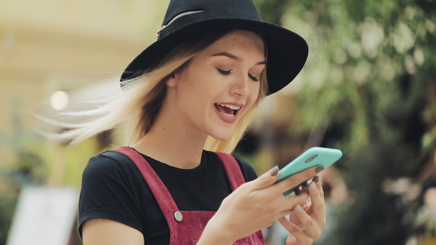 Young Pretty Blond Girl Wearing a Black Hat Using her Smartphone Voice Commander Walking at the City Street Left Side View   Shutterstock HD Video #1042266790