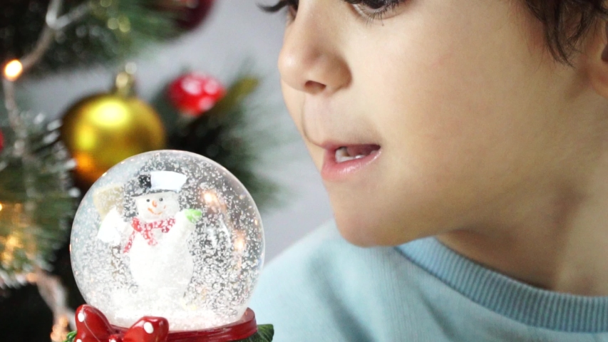 Little boy shook the snow globe, put it on the floor and peep inside it as the snow falls on the santa claus located inside this snow globe. 4K | Shutterstock HD Video #1042367290