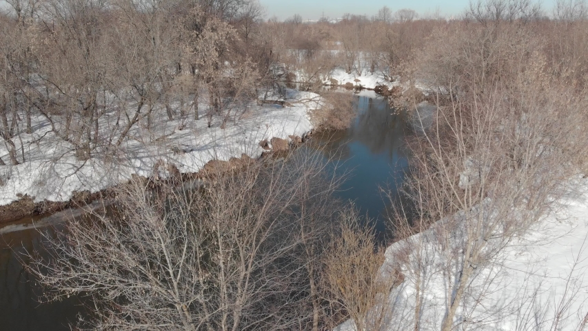 View from the quadrocopter on the river in spring. The river flows among white snow and bare trees | Shutterstock HD Video #1042372690