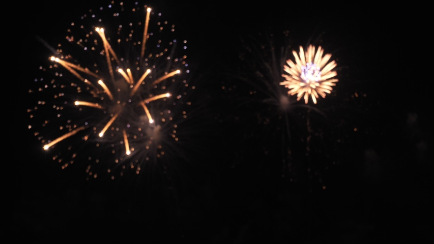 Golden big shiny fireworks with bokeh lights in the night sky. Glowing firework show. New Year's Eve fireworks celebration. Fireworks Festival. | Shutterstock HD Video #1042484770