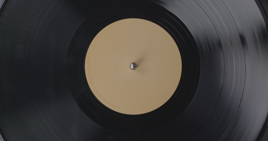 Black vinyl background with a beige screen in the center. A vinyl record on DJ turntable record player close up. The rotating plate and stylus with the needle close-up. Macro shot and view from above. | Shutterstock HD Video #1042490080
