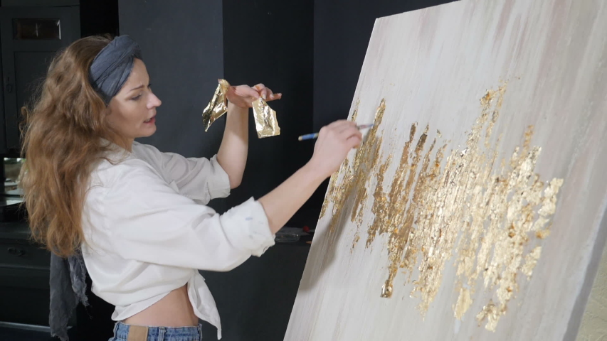 Young female artist applying gold leaf to her artwork. Artist decorates picture with tiny sheet of gold. art school, creativity and people concept. Slow motion. Shot in hd | Shutterstock HD Video #1042537570