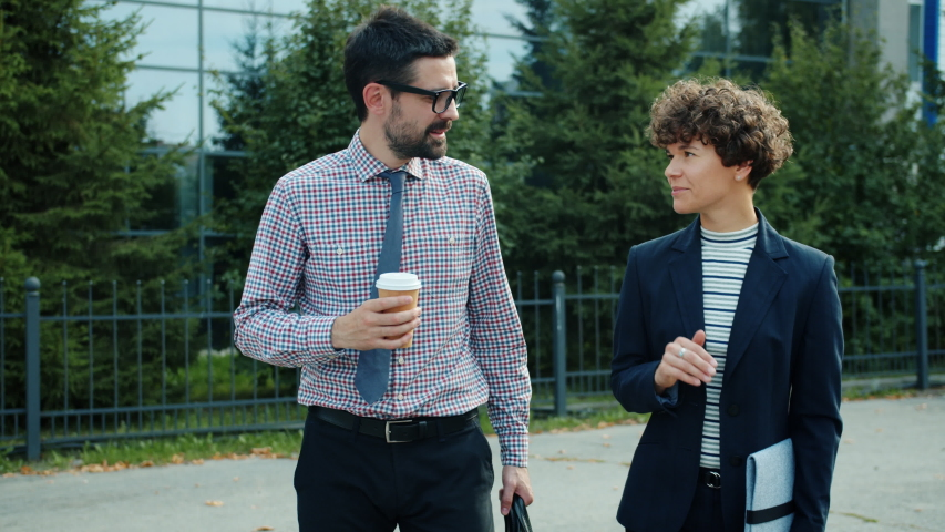 Businessman and businesswoman partners are walking outdoors talking, man is holding to go coffee discussing work smiling. People, job and communication concept. | Shutterstock HD Video #1042538770