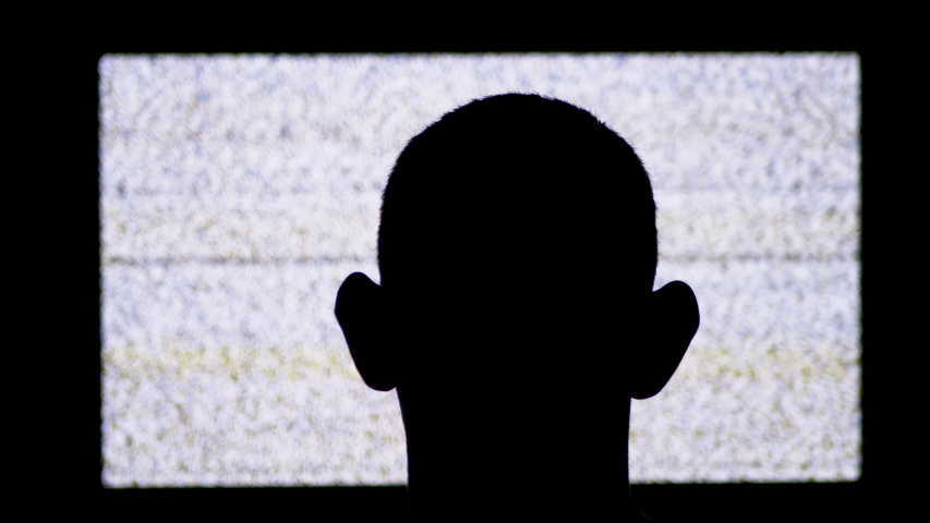Silhouette of a Man's Head is Watching White Noise and TV Interference. The man's head is watching no signal screen. Head shot of a man watching old television in the dark. Back View of men watching | Shutterstock HD Video #1042547740