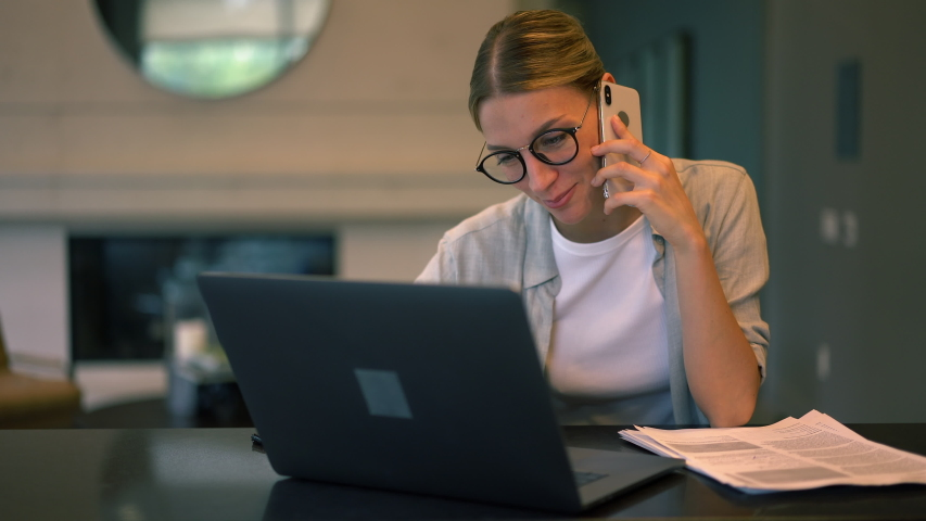 Smart casual freelancer in classic glasses communicating with colleague during paper accounting and laptop remote working, Caucasian woman using cellphone for contact phoning indoors  | Shutterstock HD Video #1042552480