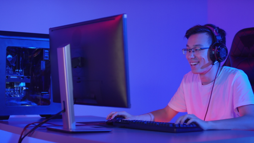Tracking right of young Asian man wearing white t-shirt and glasses sitting at PC, playing online video game and communicating with teammates | Shutterstock HD Video #1042552810
